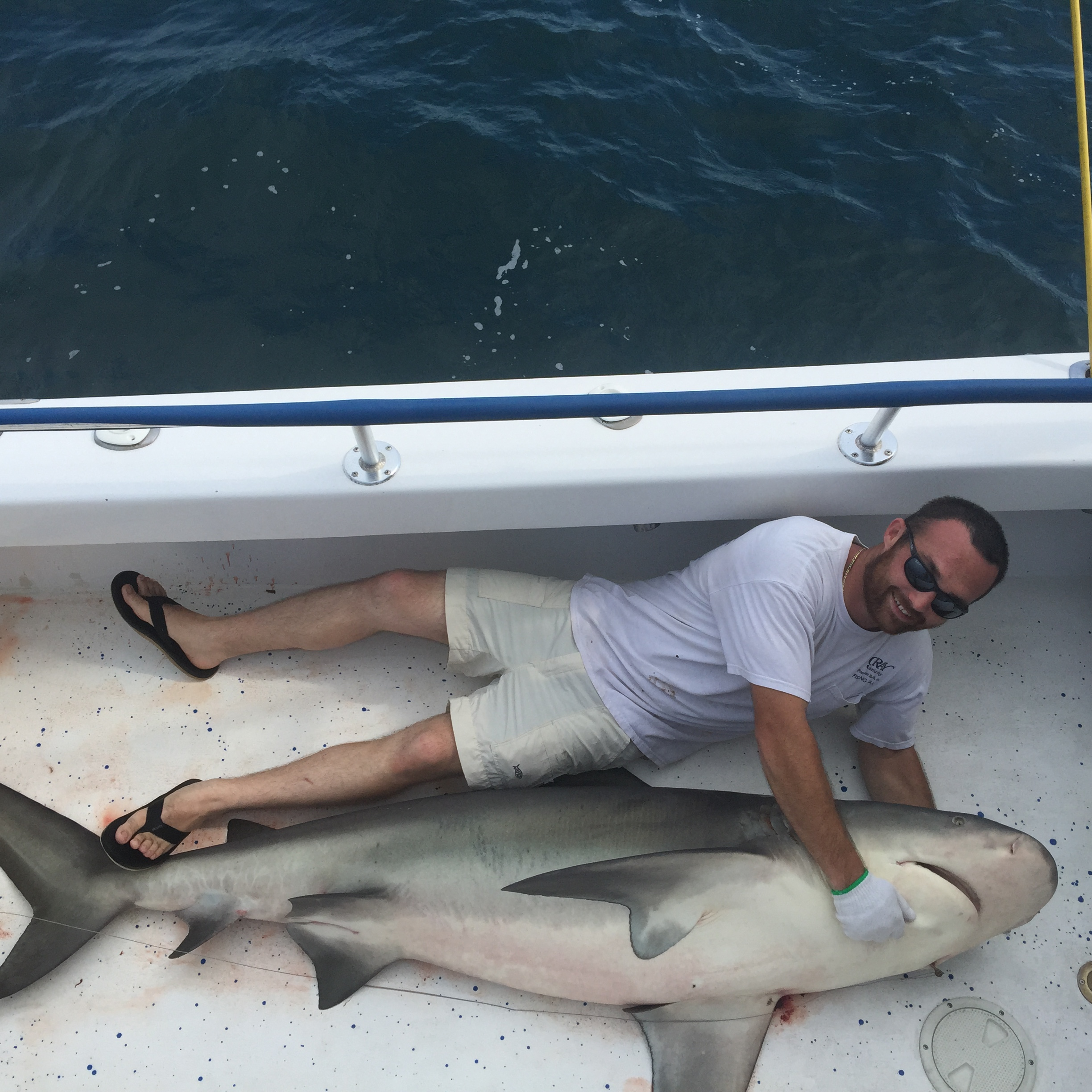 Young man lying next to a 6 foot shark he just caught
