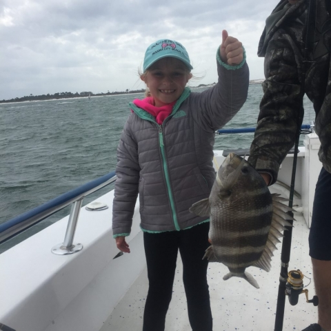 Young girl showing off her fish she just caught
