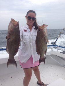 Young woman showing off 2 great fish she caught off Panama City Beach-30A
