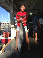 Young woman showing off large tuna she caught