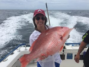 Woman holding large red Snapper she just caught