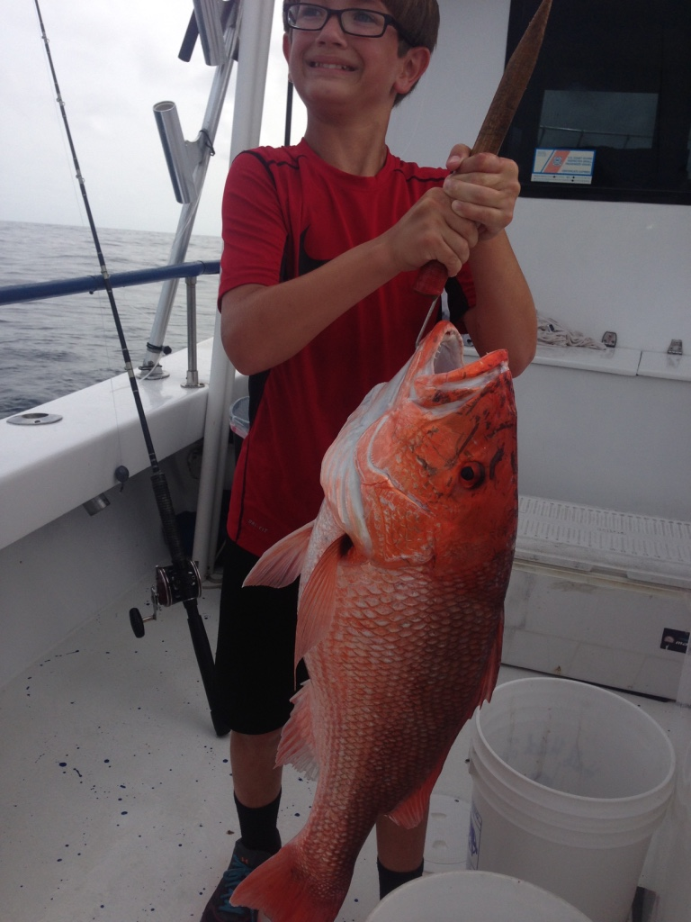 Young boy and his red snapper fishing catch