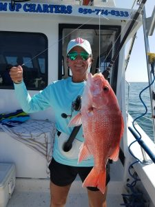 Woman holding her red snapper catch